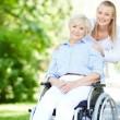 caregiver-pushing-senior-woman-in-wheelchair